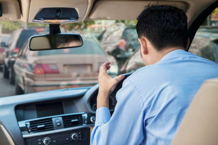 personne en colere: Vue arri�re du jeune homme furieux au volant d'une voiture sur la route � l'embouteillage Banque d'images