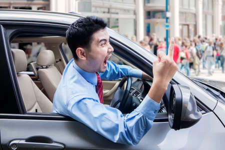 traffic accidents: Portrait of annoyed male entrepreneur screaming and showing middle finger while driving a car