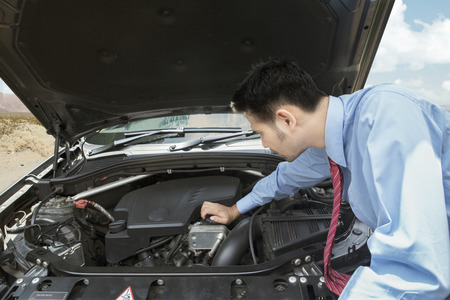 Businessman open the machine cap and checking the broken car machine on the road Stock Photo
