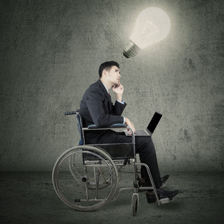 Portrait of disabled young businessman sitting on wheelchair while using laptop and looking up at light bulb photo