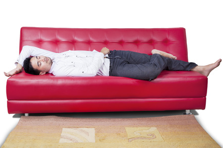Portrait of young man with casual clothes sleeping on the red sofa, isolated on white