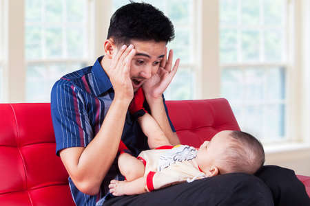 peek a boo: Portrait of young dad sitting on sofa at home while playing peekaboo with his baby boy