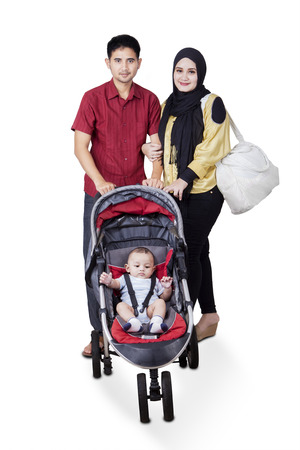 Portrait of two young muslim parents with male baby on the pram, isolated on white photo