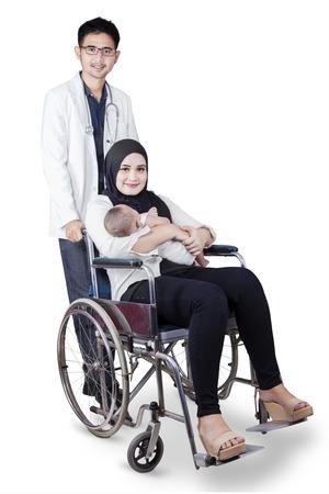 silla de rueda: Retrato de joven madre sentada en la silla de ruedas mientras sostiene a su beb� reci�n nacido con el doctor en la parte posterior