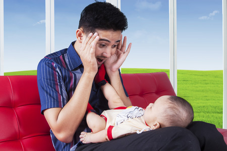 Cheerful dad sitting on sofa while playing peekaboo with his baby, shot at home