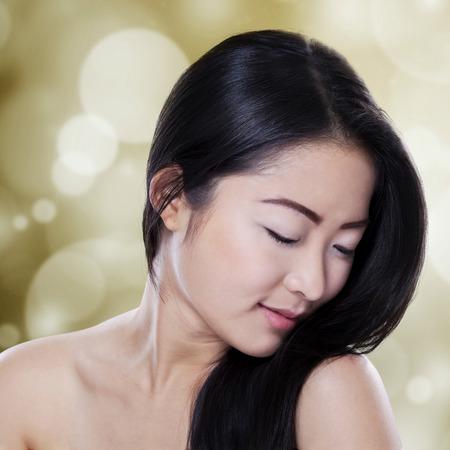 건강한 완벽한 피부와 bokeh 배경에 검은 머리카락을 가진 아시아 여성의 초상화