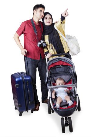 femme valise: Portrait de deux parents musulmans voyageant ensemble tout en portant leur bébé sur la poussette