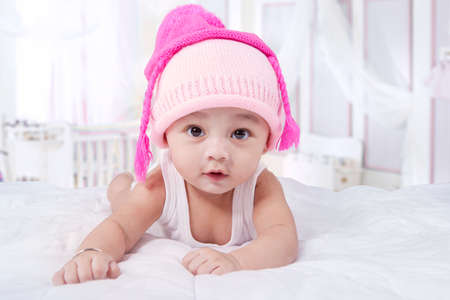 month: Cute male infant lying on bed while wearing hat and look at the camera in the bedroom Stock Photo