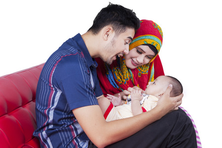 muslim baby: Portrait of two muslim parents sitting on sofa while holding their three months baby Stock Photo