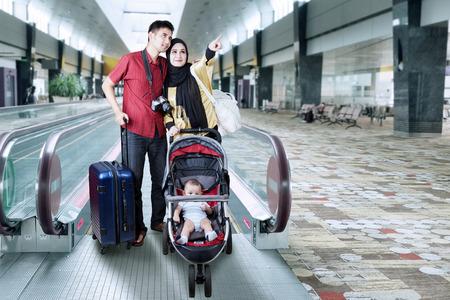 viaje familia: Retrato de dos padres vacaciones junto con su bebé en el cochecito de niño y de pie en el pasillo del aeropuerto
