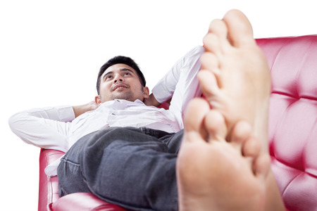 feet relaxing: Portrait of young man lying on the couch while relaxing and thinking his dreams