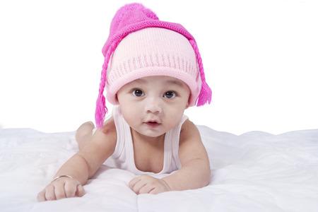 Mooie baby jongen liggend op bed terwijl het dragen van hoed met roze kleur en kijk naar de camera