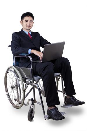 無効にする若いビジネスマン フォーマルなスーツを身に着けていると、ラップトップ コンピューターを保持しながら車椅子に座って 写真素材