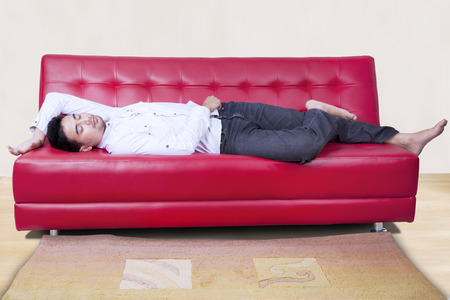 red couch: Portrait of young man sleeping on a red couch at home peacefully Stock Photo