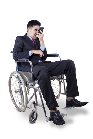 Disabled entrepreneur sitting on wheelchair and looks angry on the phone, isolated on white photo