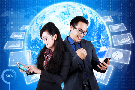 financial world: Happy businesspeople using cellphone in front of world map background with financial graph on the futuristic interface Stock Photo