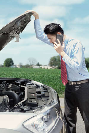 businessman waiting call: Male worker looking at the broken car machine while calling for help on the highway