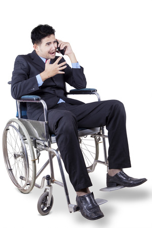 Portrait of young disabled entrepreneur sitting on wheelchair and looks scolding someone on the phone photo
