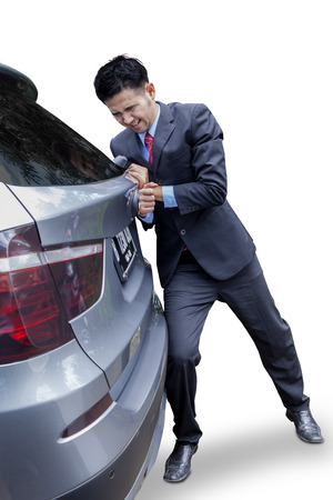 Young businessman wearing formal suit and push a broken car, isolated on white photo