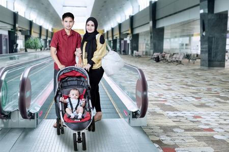 Portrait de famille musulman debout dans le hall de l'aéroport à proximité de l'escalator avec un bébé sur la poussette