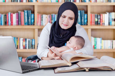 children learning: Portrait of young woman carrying baby while reading textbooks in the library