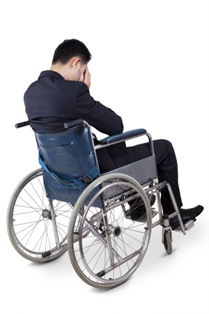 injured person: Rear view of disabled male entrepreneur sitting on wheelchair and looks unhappy, isolated on white Stock Photo