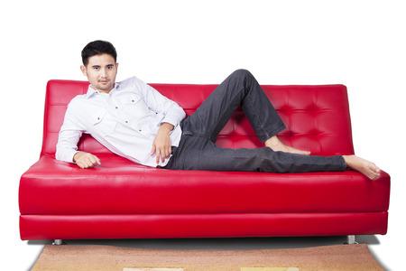 uomo rosso: Ritratto di giovane uomo sdraiato sul divano rosso con abiti casual e guardare la telecamera