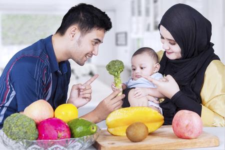 Portrait de deux parents heureux montrant des aliments sains sur leur bébé dans la cuisine