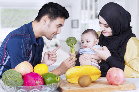 Portrait of two happy parents showing healthy food on their baby in the kitchen Stock Photo