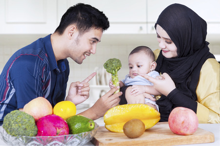 family life: Portrait of young husband with his wife giving healthy food on their baby in the kitchen Stock Photo