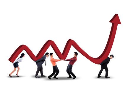 スタジオで上向きの矢印を持つビジネス グラフを持ち上げる若い起業家のグループ