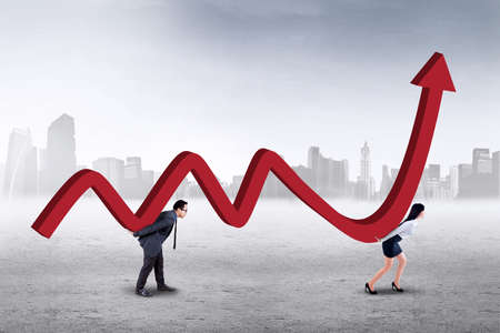 upward graph: Two young entrepreneurs work together to carry a business graph with upward arrow