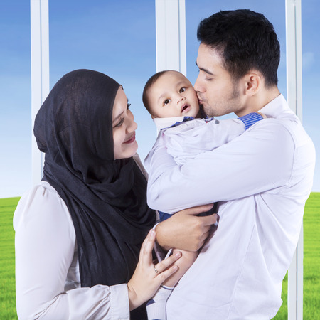 muslim baby: Two muslim parents carrying and kissing their baby near the window at home