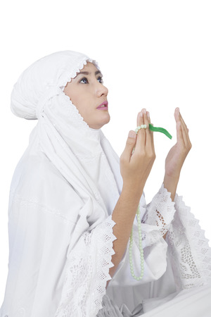 muslim pray: Portrait of female muslim wearing islamic clothes with white color to pray on the GOD