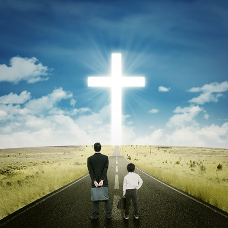 cross road: Little boy standing on the road with a businessman and looking at a cross on the end of the road