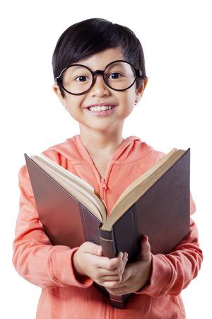 Portrait de excité petite fille lisant un livre tout en portant des lunettes et sourire sur la caméra