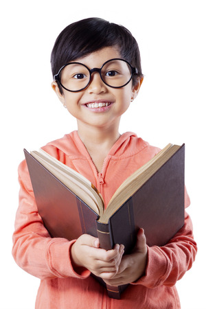 pretty little girl: Portrait of excited little girl reading a book while wearing glasses and smiling on the camera