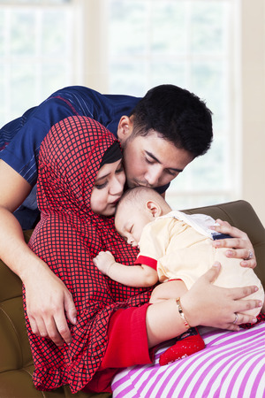 muslim baby: Portrait of two young muslim parents kiss their baby boy on the sofa at home