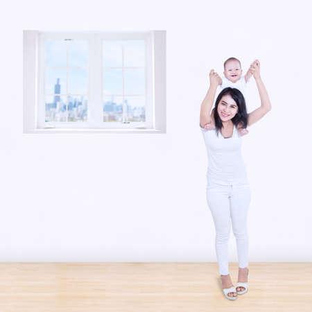 caras felices: Asiática sonriente madre jugando con su bebé en casa