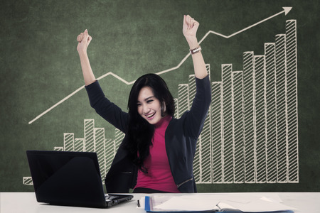 winning business woman: Happy winning business woman working on her laptop with graph background Stock Photo
