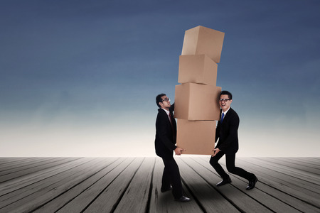 carrying heavy: Team work concept; Two Asian business men carrying heavy boxes