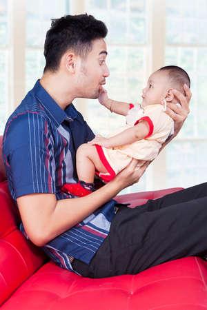 niños chinos: Padre joven feliz sentado en el sofá, mientras que la celebración de su bebé, un disparo en la sala de estar en casa