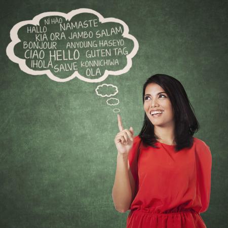 languages: Retrato de estudiante de secundaria femenina que señala en la burbuja nube de multi idioma. Concepto de múltiples aprendizaje de idiomas