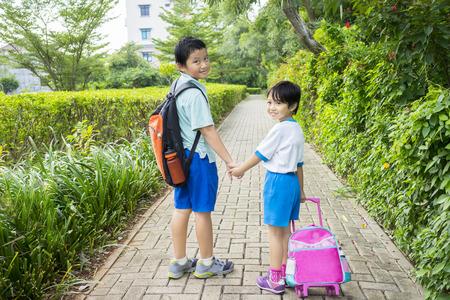 üniforma: İki sevimli küçük öğrenci yolda yürürken okula gitmeyi ve birlikte el ele tutuşmuş portre Stok Fotoğraf