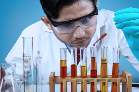 combining: Asian scientist combining the chemical fluid using a pipette into test tube