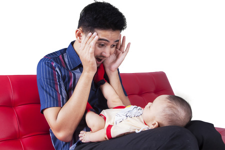 peekaboo: Young father sitting on the sofa while playing peekaboo with his baby boy, isolated on white