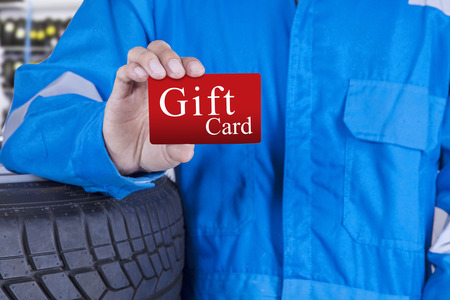 service card: Closeup of male workshop worker with blue uniform, showing a gift card