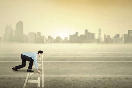 liderazgo empresarial: Empresario joven en la posición lista para correr y competir en la pista Foto de archivo