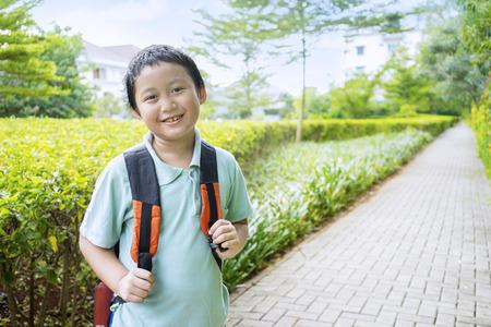 ir al colegio: Retrato del ni�o peque�o que sonr�e en la c�mara mientras llevaba mochila, un disparo en el parque