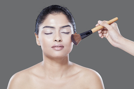 beauty and health: Attractive female model closed her eyes when her assistant applying makeup powder on her face
